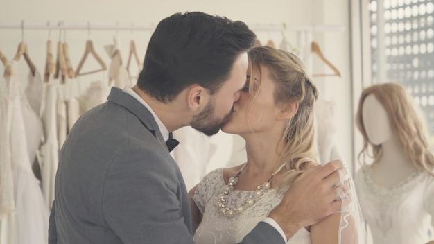 Glückliche braut und bräutigam im hochzeitskleid bereiten sich auf die hochzeit vor