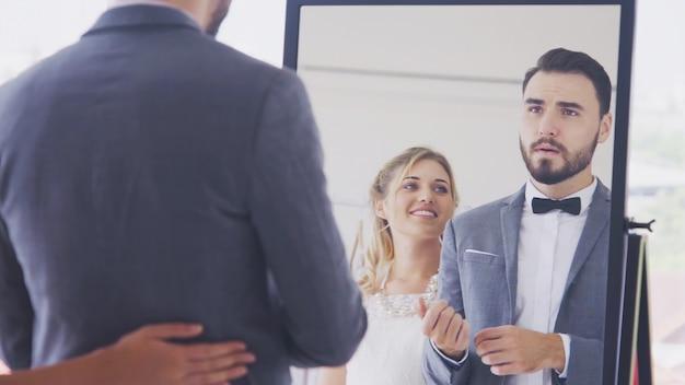 Glückliche braut und bräutigam im hochzeitskleid bereiten sich auf die hochzeitszeremonie vor