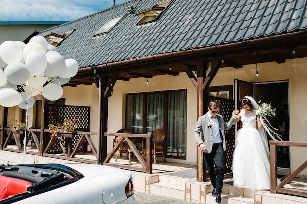 Glückliche braut und bräutigam kamen in einem haus außerhalb der stadt an