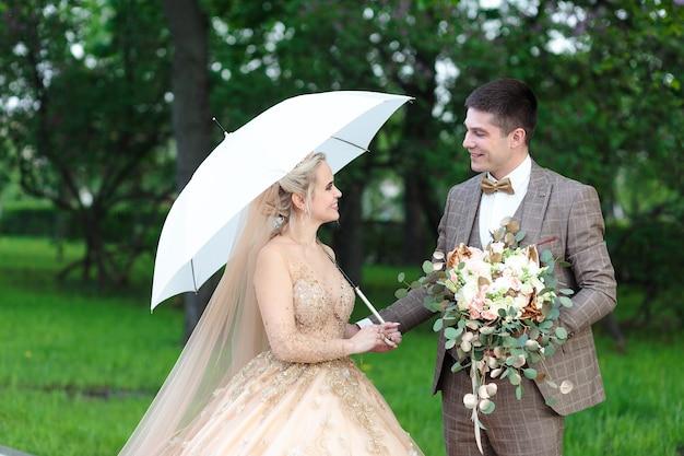 Glückliche braut und bräutigam mit einem weißen regenschirm im regen, im sommer im park. open-air-hochzeit.