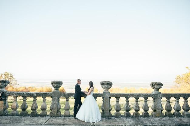Glückliche braut und bräutigam nahe dem mittelalterlichen palast an ihrem hochzeitstag