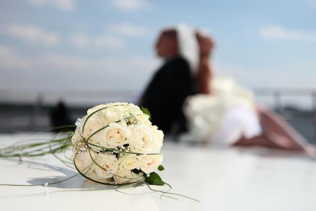 Glückliche braut und bräutigam sitzen auf der yacht mit einem hochzeitsblumenstrauß