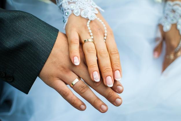 Glückliche braut und bräutigam zeigen ihre ringe