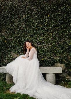 Glückliche brautfrau in einem hochzeitskleid, das aufwirft