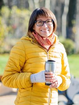 Glückliche breite lächelnde frauen im hellen gelben jacketis, der thermosbecher hält
