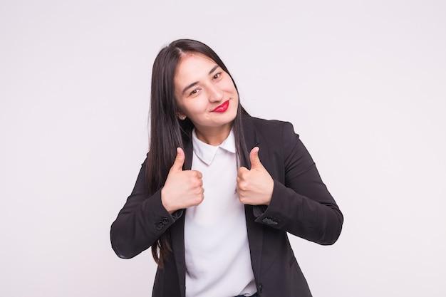 Glückliche brünette asiatische frau mit roten lippen und daumen hoch in weiß mit kopienraum