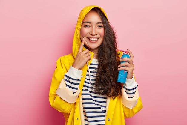 Glückliche brünette dame heilt halsschmerzen mit spray, gekleidet in gelbem regenmantel mit kapuze, krank, nachdem sie lange zeit im freien während des regnerischen tages verbracht hat