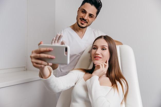 Glückliche brünette frau an der schönheitsklinik spricht sie mit arzt über gesichtsästhetikbehandlung