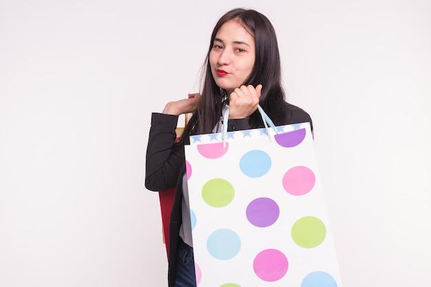 Glückliche brünette frau des einkaufsverkaufskonzeptes, die formelle kleidung mit einkaufstaschen auf weiß trägt