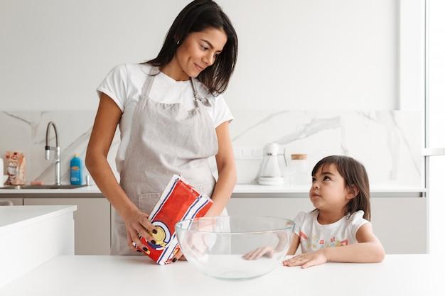 Glückliche brünette frau, die schürze trägt, die mit ihrer kleinen tochter zusammen in der küche zu hause kocht