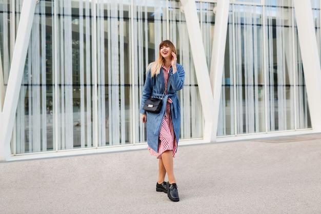 Glückliche brünette frau im blauen mantel und im roten kleid, die entlang der modernen straße gehen