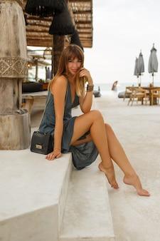 Glückliche brünette frau im sexy kleid, das im stilvollen strandrestaurant im \ bali-stil aufwirft. volle länge.