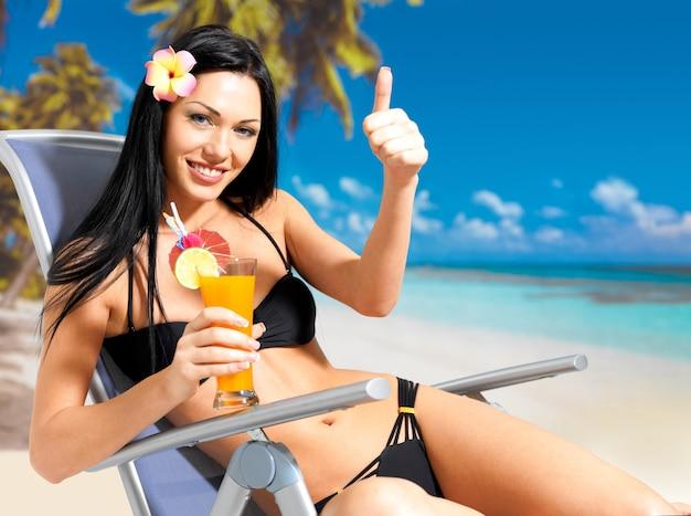 Glückliche brünette frau im urlaub am strand mit daumen hoch zeichen