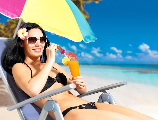 Glückliche brünette frau im urlaub, die orangensaft am strand trinkt