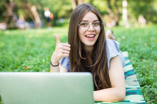 Glückliche brünette frau in den brillen, die auf gras im park mit laptop-computer liegen und daumen oben zeigen