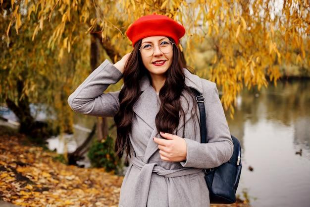 Glückliche brünette frau in der stilvollen roten baskenmütze