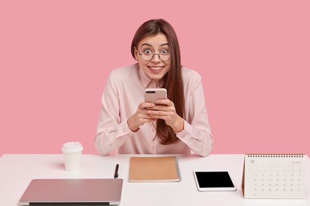 Glückliche brünette frau wählt nummer, hält modernes handy, chattet in sozialen netzwerken, hat ordentlich arrangiert