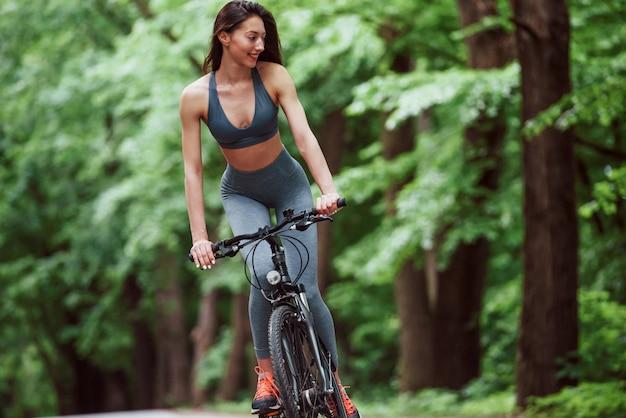 Glückliche brünette. weiblicher radfahrer auf einem fahrrad auf asphaltstraße im wald am tag