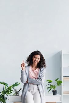 Glückliche brunettefrau, die oben an arbeitsplatz zeigt