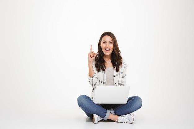 Glückliche brunettefrau im hemd, das auf dem boden mit laptop-computer beim haben der idee und betrachten der kamera über grau sitzt