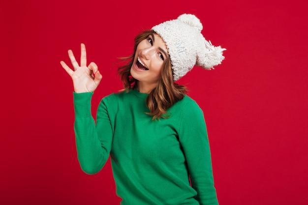 Glückliche brunettefrau in der strickjacke und in lustigem hut, die ok darstellen