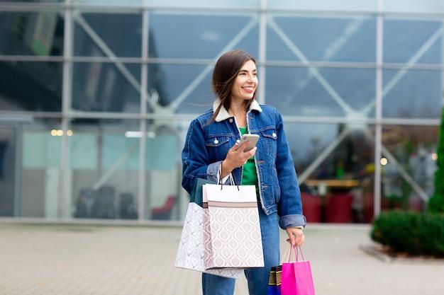 Glückliche brunettefrau mit einkaufstaschen und mobiltelefon genießend im einkaufen. einkaufen, lifestyle-konzept