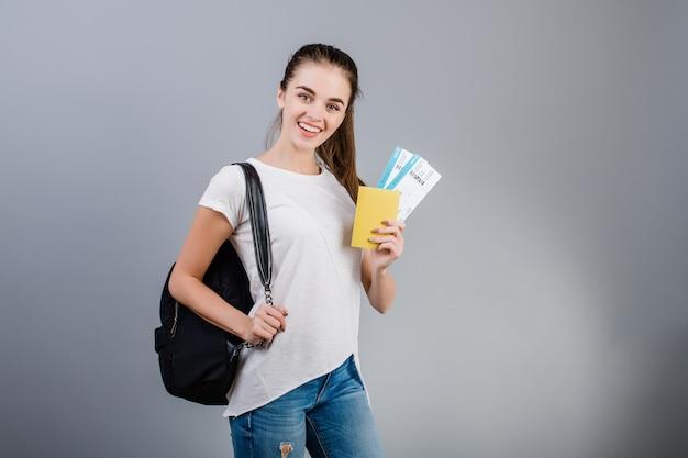 Glückliche brunettefrau mit flugtickets im pass und in rucksack lokalisiert über grau