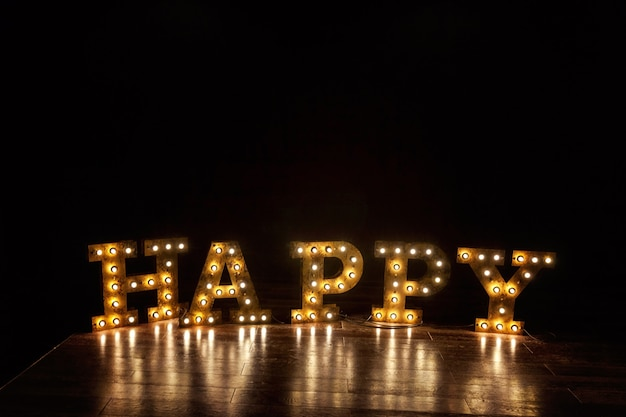 Glückliche buchstaben wort glühenden licht retro glühbirnen stehen auf dem boden. moderne innenarchitekturwohnung des dunklen klassischen stils mit glühbirnenhintergrund der retro-lampen