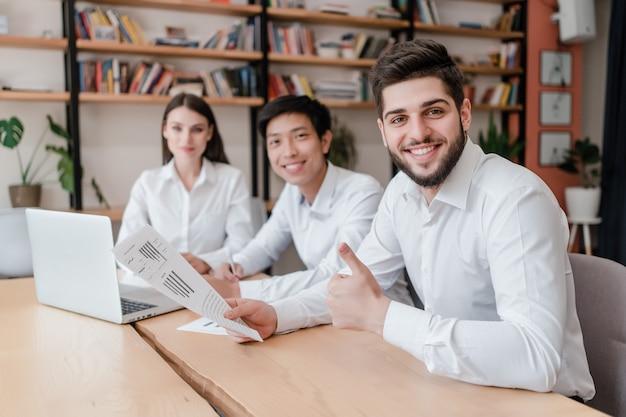 Glückliche büroangestellte am arbeitsplatz, der zusammen arbeit erledigt