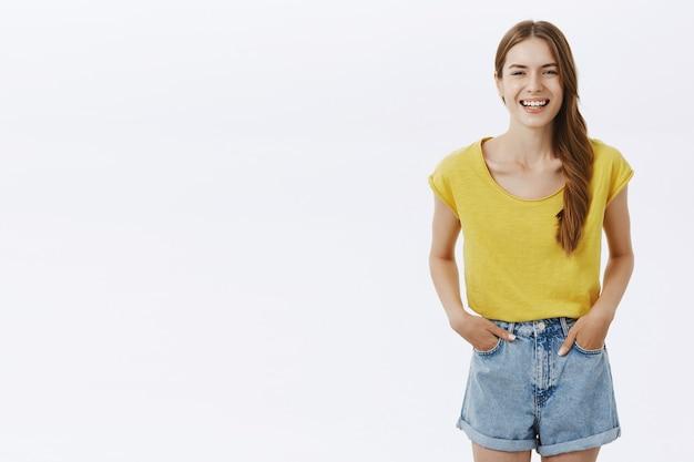 Glückliche charmante freundlich aussehende frau mit geflochtenem haar, das im gelben t-shirt und in den lächelnden shorts posiert, entzückte händchenhalten in den beiläufig stehenden taschen