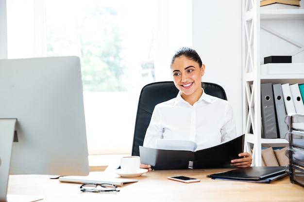 Glückliche charmante geschäftsfrau, die dokumente hält und auf den computerbildschirm schaut, während sie am schreibtisch sitzt