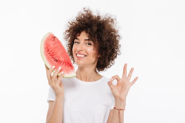 Glückliche cheerfuwoman mit lockigem haar, das wassermelonenscheibe hält