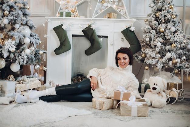 Glückliche dame, die auf boden zu hause auf dem hintergrund des weihnachtsbaumes liegt