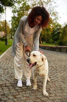 Glückliche dame, die ihren weißen freundlichen hund beim gehen im park umarmt