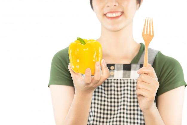 Glückliche dame, die küchenmaterial über kopienraumhintergrund hält