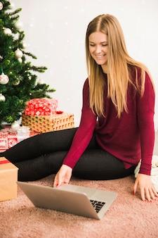 Glückliche dame, die laptop nahe geschenkboxen und weihnachtsbaum verwendet