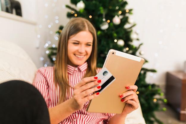 Glückliche dame, die tablette und kreditkarte nahe weihnachtsbaum hält Kostenlose Fotos