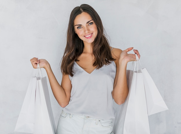 Glückliche dame im unterhemd, das einkaufstaschen hält