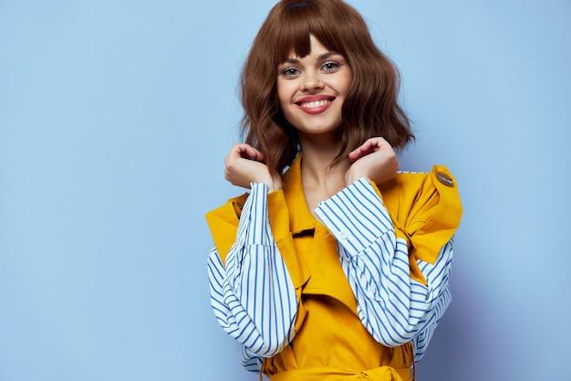 Glückliche dame in einem modischen mantel hält ihre hände nahe an ihrem gesicht und lächelt auf blau