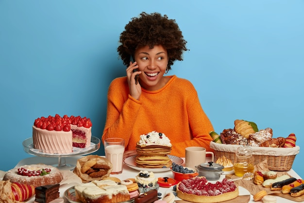 Glückliche dame mit afro-haarschnitt hat angenehme unterhaltung per handy, genießt es, leckere kuchen zu essen, überlegt, pfannkuchen mit sahne zu essen, süß zu sein, isoliert an der blauen wand.