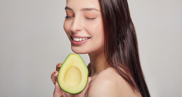 Glückliche dame mit avocado und lächeln mit den zähnen