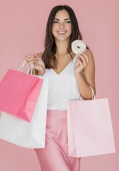 Glückliche dame mit einkaufstüten und einem donut