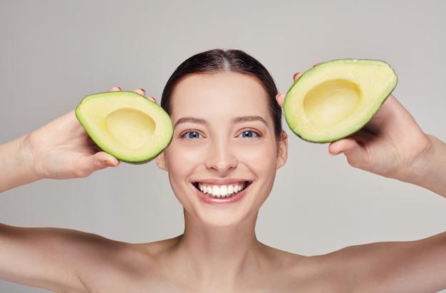 Glückliche dame mit perfektem lächeln mit avocado in den händen