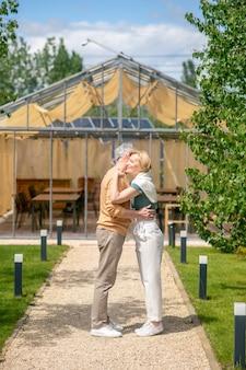 Glückliche dame mittleren alters, die draußen ihren mann umarmt