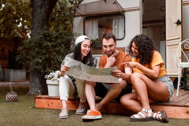 Glückliche drei freunde, die auf einer karte vor van long shot suchen