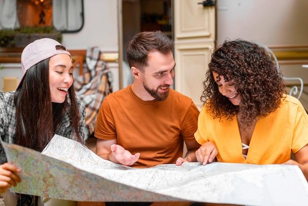 Glückliche drei freunde, die eine karte betrachten