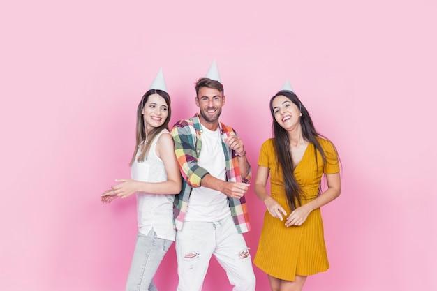 Glückliche drei freunde, die gegen den rosa hintergrund zusammen tanzen in der party stehen