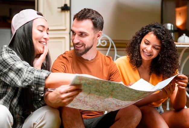 Glückliche drei freunde, die nach orten suchen, um auf einer karte zu gehen