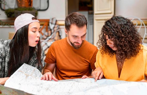 Glückliche drei freunde mit einer karte