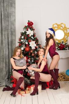 Glückliche drei schöne mädchen mit unterschiedlicher haarfarbe, schneemädchen in einem weihnachtskostüm mit geschenktüte.